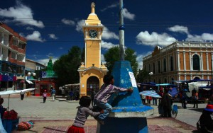 The Uyuni town square in the sunshine in December, 2005. Features children playing by a small monument and a beautiful colonial-style building in the background.